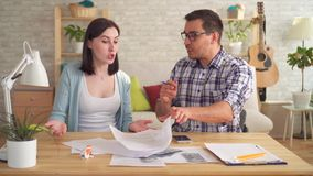 Young couple quarrels while making calculations of documents at home with a calculator