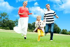 Young couple racing with their daughter Royalty Free Stock Images
