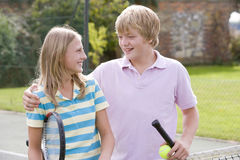 Young couple with rackets on tennis court smiling Royalty Free Stock Photo