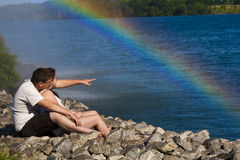 Young Couple with a rainbow. A young couple embrace by the water with a rainbow in the background royalty free stock photos