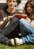 Young couple read the guidebook sitting near car. Closeup image of young couple sitting on grass near the car and read guidebook stock images
