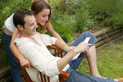 Young couple reading a book. Young man and young woman reading a book together in the garden Royalty Free Stock Photos