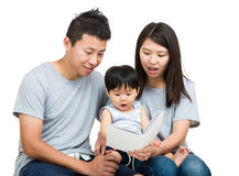 Young couple reading book with baby boy. Isolated on white Stock Images