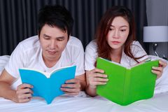 Young couple reading a book on bed in bedroom. Young couple reading a book on bed in the bedroom Royalty Free Stock Photos