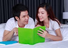 Young couple reading a book on bed in bedroom. Young couple reading a book on bed in the bedroom Stock Photos