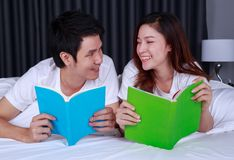 Young couple reading a book on bed in bedroom. Young couple reading a book on bed in the bedroom Royalty Free Stock Image