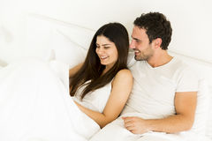 Young couple reading a book in the bed. Lovely young couple reading a book in the bed Stock Images