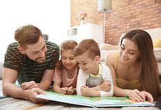 Young couple reading book with children. Happy family stock image