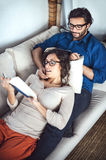 Young couple reading book on couch at home Royalty Free Stock Photos