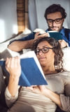 Young couple reading book on couch at home Stock Photos