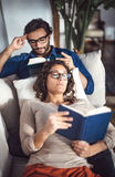 Young couple reading book on couch at home Stock Image