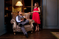 Young couple reading book on couch at home. Pregnant wife asks her husband's attention Stock Photos