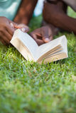 Young couple reading book on the grass. On a sunny day Royalty Free Stock Photos