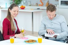 Young couple reading book while having breakfast in kitchen. Young Stock Photos