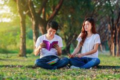Young couple reading a book and listening music with earphones i. N the park Stock Photos