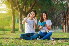 Young couple reading a book and listening music with headphone i. N the park Stock Photos