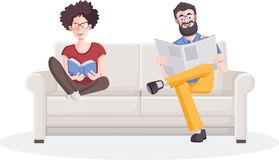 Young couple reading book and newspaper. On sofa Stock Photos