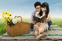 Young couple is reading book outdoors Royalty Free Stock Image