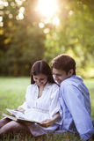 Young couple reading a book in a park Stock Image