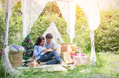 Young couple reading book with a present in the park Royalty Free Stock Photo