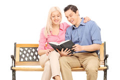 Young couple reading a book seated on bench Royalty Free Stock Photography