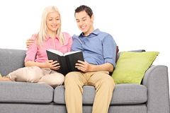 Young couple reading book seated on a couch. Isolated on white background Royalty Free Stock Image
