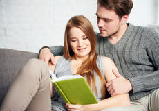 Young Couple Reading a Book On Sofa Royalty Free Stock Photos