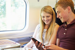 Young Couple Reading A Book On Train Journey. Smiling Royalty Free Stock Photo