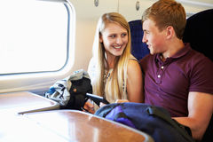 Young Couple Reading A Book On Train Journey. Smiling Royalty Free Stock Photography
