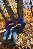 Young couple reading book under the old tree. Young couple reading book in autumn park, boy and girl resting and having picnic in the forest, girl drinking tea Stock Photography