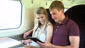 Young Couple Reading E Book On Train Journey Stock Images