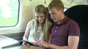 Young Couple Reading E Book On Train Journey Royalty Free Stock Photos