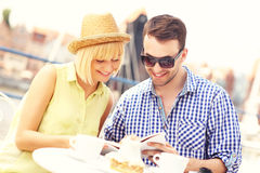Young couple reading a guide in a restaurant Stock Image