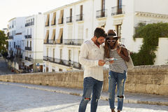 Young couple reading a guidebook in the street, Ibiza, Spain Stock Photo