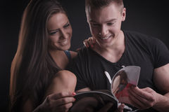 Young couple reading magazine Royalty Free Stock Image