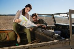 Young couple reading map in off road vehicle. On landscape stock photos