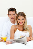 Young couple reading a newspaper Stock Photos