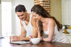 Young couple reading newspaper while having breakfast Stock Photos