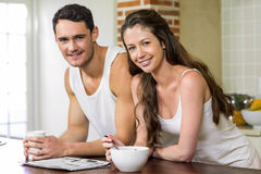 Young couple reading newspaper while having breakfast Stock Photography