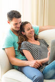 Young couple reading newspaper on sofa Stock Images
