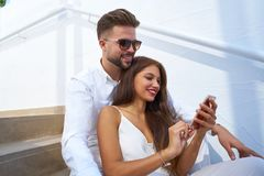 Young couple reading smarphone in a stairway. Young couple reading smarphone in a white stairway outdoor Royalty Free Stock Photos