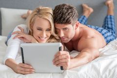 Young couple reading a tablet in bed Royalty Free Stock Photo