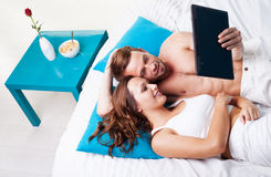 Young couple reading a tablet screen Stock Images