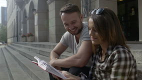 Young couple reading together while sitting on university stairs, outdoors. Young couple during a break sitting against the building of the University. Young stock footage