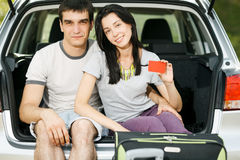 Young couple ready for road trip. Young smiling couple sitting in the opened car bloom holding empty credit cards Stock Image