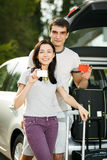 Young couple ready for road trip. Young couple standing near the opened car boot with suitcases, showing blank credit cards, outdoors Royalty Free Stock Image