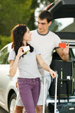 Young couple ready for road trip. Young couple standing near the opened car boot with suitcases, holding blank credit cards, looking at each other, outdoors Stock Photos