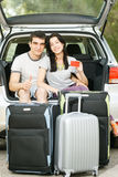 Young couple ready for road trip. Young smiling couple sitting in the opened car bloom with travel suitcases holding empty credit card Royalty Free Stock Photography
