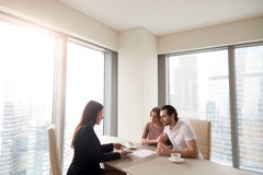 Young couple and real estate agent manager discussing contract a Stock Photography