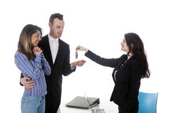 Young couple receives keys from female real estate agent Stock Photography